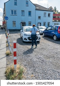 MOERS / GERMANY - AUGUST 16 2019 : German parking inspector taking notes to issue a parking fine.