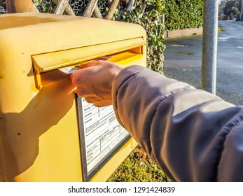 MOERS / GERMANY - JANUARY 18 2019 : Lady throwing a letter into the standard yellow letterbox of German Postal Service.