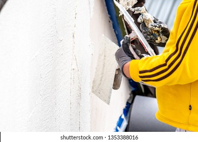 MOERS / GERMANY - MARCH 26 2019 : Construction worker plastering and smoothing concrete wall with cement.