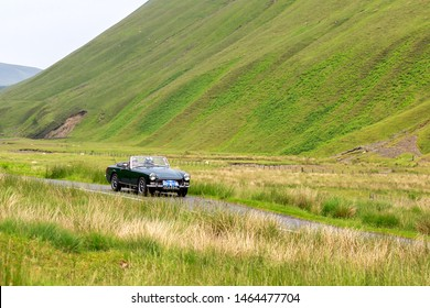MOFFAT, SCOTLAND - JUNE 29, 2019: 1972  MG Midget Sports car in a classic car rally en route towards the town of Moffat, Dumfries and Galloway