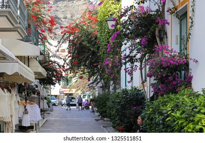 Mogan,Gran Canaria,02.06.2019.Typical street with multi-coloured bougainvillea plants and shops in the Harbour of Mogan,which is the most picturesque and pretty resort of the island.