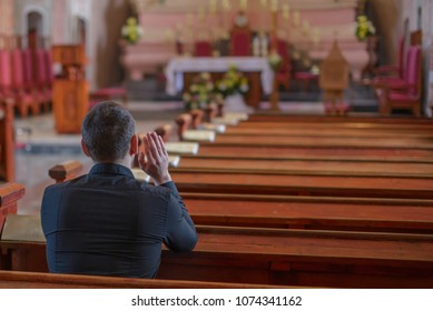 Mogilev, Belarus - 13.04.2018: a young man or priest in a black shirt sits on a wooden bench and prays inside the Catholic Church