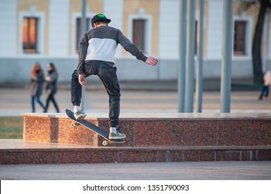 Mogilev, Mogilev / Belarus -  March 23 2019: A teenager skateboarder does an flip trick in a skatepark on at sunrise city
