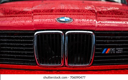 MOGYOROD, HUNGARY - JUNE 16: An old BMW M3 on display during a DTM race weekend after a short rain. Wet BMW logo, classic sports car.