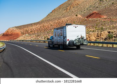Mohave desert by Route 66. RV Camping, Camper Van on road. Caravan or recreational vehicle motor home trailer on a mountain road in America
