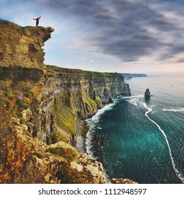 Mohers Cliffs - Ireland: Silhouette of woman on the top of the hill over the sea