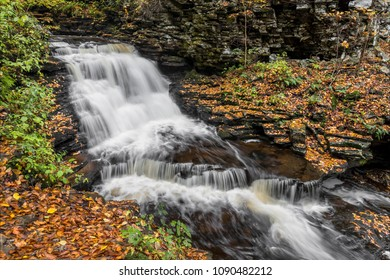 Mohican Falls, a beautiful waterfall in Ganoga Glen at Pennsylvania's Ricketts Glen State Park, is surrounded by colorful fall foliage.