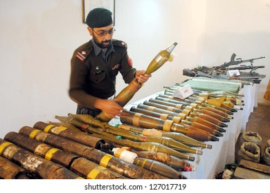 MOHMAND AGENCY, PAKISTAN - FEB 04: Security official show seized weapons and  explosive material, which were recovered in military search operation on February 04, 2013 in Mohmand Agency.