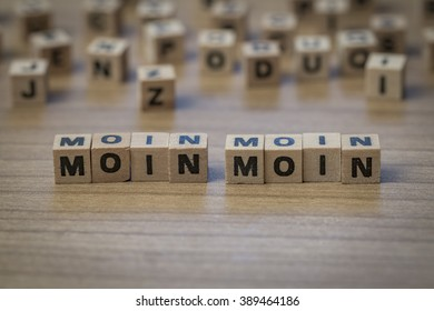moin moin, traditional regional greeting (simmilar to hello) in the northern part of germany written in wooden cubes on a table