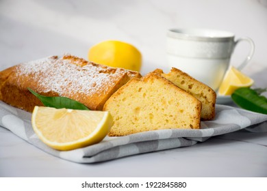 Moist lemon pound cake on kitchen towel on marble table with slices of lemon and cup of tea on plate. Delicious breakfast, traditional tea time treat. Reciepe of English lemon pie loaf.