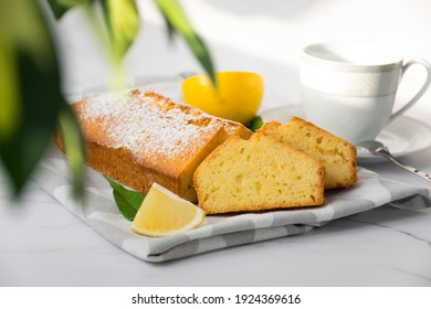 Moist lemon pound cake on towel, lemons and cup on marble table through house plant leaves. Delicious breakfast, traditional tea time treat. Reciepe of American lemon pie loaf.