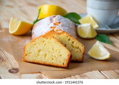 Moist lemon pound cake with sugar powder on parchment on rustic wooden background with slices of lemon and cup of tea on plate. Delicious breakfast, traditional English tea time. Reciepe of lemon pie.