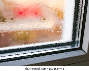 Moist word written on wet window. High level of dampness in apartment. Window glass with high air humidity. Background of natural water condensation