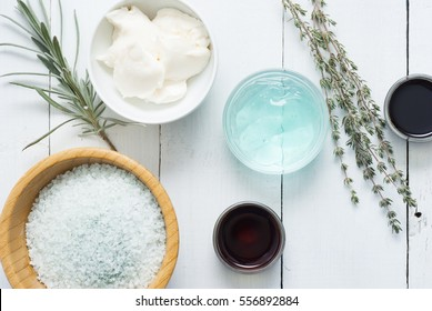 moisturizer, bath salt,  night cream, pumpkin seed oil with lavender and thyme leaves on white wood background
