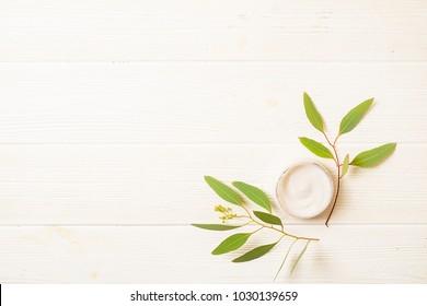 Moisturizer face body skin care wrinkle cream & eucalyptus leaves on white wood textured table background. Retinol moisturizing anti aging antioxidant skincare product for women. Copy space, close up.