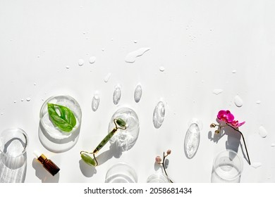 Moisturizer, green jade face roller with exotic monstera leaves, orchid flowers and glass baubles. Sunshine, long shadows. Flat lay on off white background with text space. Face lymph drainage