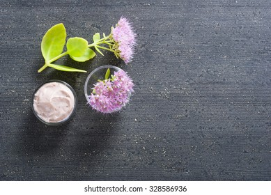 moisturizer with pink flowers on old black wood table