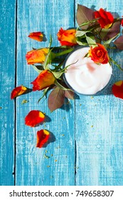 moisturizer and rose flowers on blue wooden table background