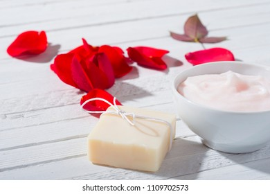 moisturizer, soap and rose petals on white wooden table