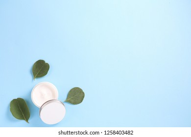Moisturizing care skincare face cream for healing complicated troubled skin type in an open jar with visible texture. Copy space, close up, background, flat lay, top view. Eucalyptus leaf decoration.