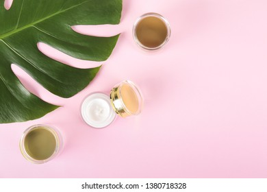 Moisturizing care skincare face cream for healing complicated troubled skin type in an open jar with visible texture. Copy space, close up, background, flat lay, top view. Monstera leaf decoration.
