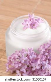 Moisturizing face cream with lilac blossom on bamboo mat