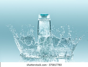 Moisturizing shampoo for dry hair. The  bottle of clear liquid stays on the turquoise water background with big  splash