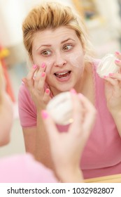 Moisturizing skin care, cosmetics, dermatology concept. Woman applying face cream with her finger