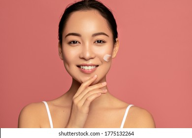 Moisturizing. Young beautiful asian model posing with applayed cream on her face