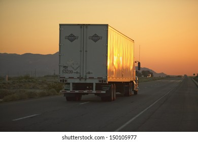 MOJAVE DESERT, CA - JULY 29: 18-wheeler semi-trucks at sunset hit the highway driving down Interstate Highway 15 between Los Angeles and Las Vegas Nevada on July 29, 2004 in Southern California