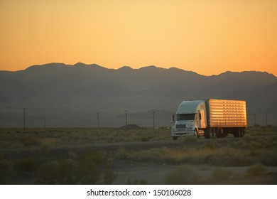 MOJAVE DESERT, CA - JULY 29: 18-wheeler semi-trucks hit the highway at sunset driving down Interstate Highway 15 between Los Angeles and Las Vegas Nevada on July 29, 2004 in Southern California