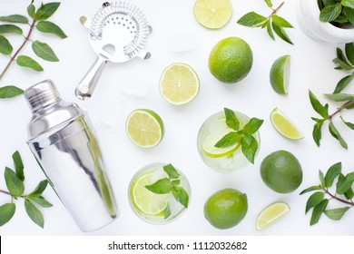 Mojito cocktail alcohol bar long drink making. Mint, lime, rum, ice ingredients, juice, soda water, shaker and bar utensils on white background. Top view. Flat lay.