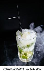 Mojito cocktail at the bar. Mojito cocktail on black background. Cocktail Mojito at the nightclub. Ice cold Mojito.