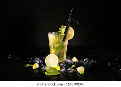 Mojito cocktail at the bar. Mojito cocktail over black background. Cocktail Mojito in the nightclub. Ice cold Mojito.