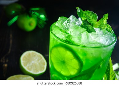 Mojito cocktail, closeup fresh drink with lime, mint and ice on wooden table on black background
