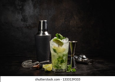 Mojito cocktail decorated with lime and mint leaves. Alcoholic drink concept. Dark Rustic Style