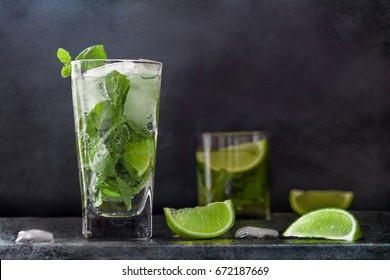 Mojito cocktail drink with lime Ice and mint on dark background with Copy space