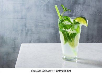 Mojito Cocktail - a Drink Made with Rum, Limes, Mint, Simple Syrup, and Soda Water - in Glass on Marble Bar Counter with Copy Space