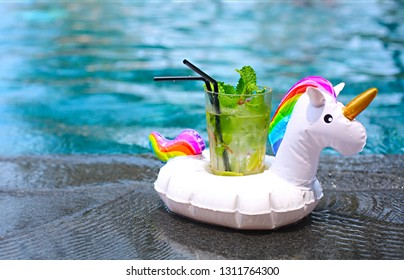 Mojito cocktail at the edge of a resort pool in inflatable unicorn. Concept of luxury vacation. Outdoor pool background