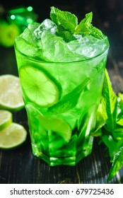 Mojito cocktail, fresh drink with lime, mint and ice on wooden table on black background