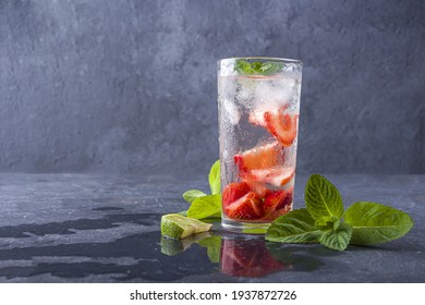 Mojito cocktail with ice cubes. Glass of Summer lemonade or ice tea. Refreshing cool detox drink with strawberry, lime and mint on dark background. Healthy eating. Ð¡opy space for text