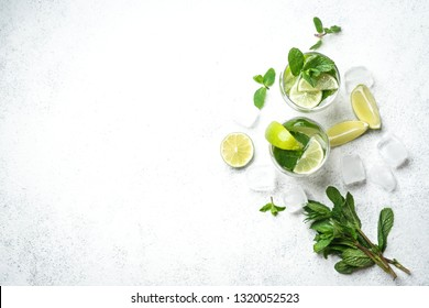 Mojito cocktail with ice, mint and lime on a light background Top view Copy space.