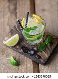 Mojito cocktail with lime, lemon and mint in a glass on a dark rustic background. Fresh summer cocktail. Lemon mojito
