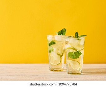 Mojito cocktail with lime and mint in highball glass on wooden table. Yellow background. Space for text