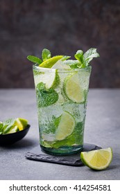 Mojito cocktail with lime and mint in highball glass on a grey stone background