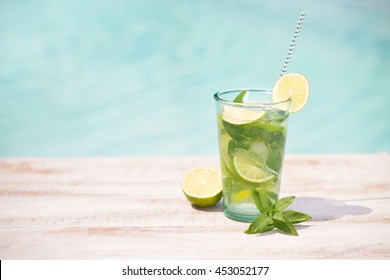 Mojito cocktail with lime and mint in highball glass on tre beach  background Copy space