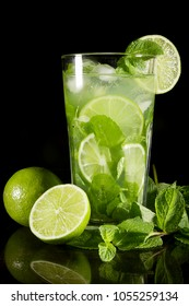 Mojito cocktail and lime on a black reflective surface