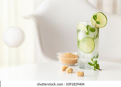 Mojito cocktail with lots of ice, white rum, lemon juice and tonic, decorated with lime slices and mint leaves on a modern white table