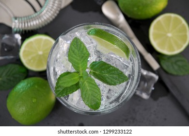 Mojito cocktail making. Mint, lime, ice ingredients and bar utensils on dark stone table