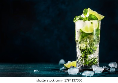 Mojito cocktail or mocktail with lime, mint, and ice in glass on blue background. Summer cold alcoholic non-alcoholic drink,  beverage and cocktail. Copy space